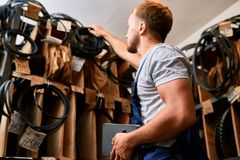 Mechanic Choosing Parts in Storage Room. Low angle  portrait of young mechanic  inspecting stock while doing inventory in industrial tools store Royalty Free Stock Image