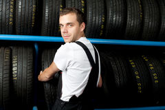 Mechanic choosing tire in car service. Young mechanic choosing tire in car service Stock Photos