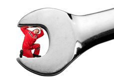 Mechanic clamped inside big spanner Stock Images