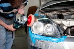 Mechanic cleaning headlights and polishing with power buffer Royalty Free Stock Image