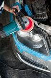 Mechanic cleaning headlights with polishing power buffer machine Stock Image