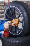 Mechanic cleaning the rim of tire Royalty Free Stock Photography
