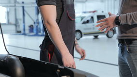 Mechanic and client shake hands. Close up of mechanic and client shaking each others hands at the car service. Man dressed in black overalls and man dressed in stock footage