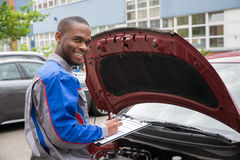 Mechanic With Clipboard In Front Of A Car. Young African Mechanic Writing On Clipboard In Front Of Open Car Engine royalty free stock photography