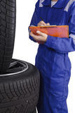 Mechanic with clipboard inspecting tires Stock Photography