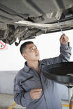 Mechanic Concentrating and Changing the Oil Royalty Free Stock Photo