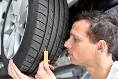 Mechanic controls tread depth of a car tyre. Closeup Royalty Free Stock Photography