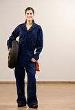 Mechanic in coveralls holding tire Stock Image