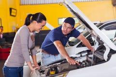 Mechanic customer car. Friendly mechanic showing female customer her car problem in garage royalty free stock image