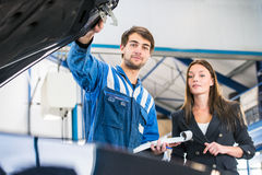 Mechanic and customer looking under the hood of a car. Mechanic, taking a look under the hood of a business woman's car with an order form and pen in his hand Stock Photos