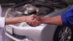 Mechanic and customer shaking hands in an auto repair shop. stock video