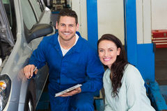 Mechanic and customer smiling at camera Stock Photography