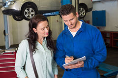 Mechanic and customer talking together Royalty Free Stock Images