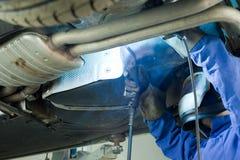 Mechanic Cuts Off The Muffler In The Car. Stock Photo