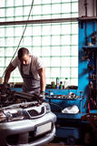Mechanic diagnosing car engine. Picture of young mechanic diagnosing car engine Royalty Free Stock Photography