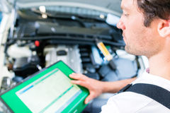 Mechanic with diagnostic tool Royalty Free Stock Image