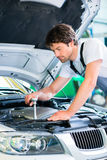 Mechanic with diagnostic tool in car workshop Royalty Free Stock Photo