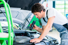 Mechanic with diagnostic tool in workshop Stock Photography