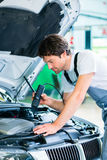 Mechanic with diagnostic tool in workshop Stock Images