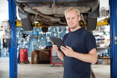 Mechanic with digital tablet. Portrait of young mechanic holding digital tablet in his auto repair shop stock photo
