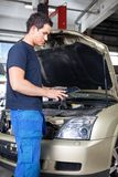 Mechanic with digital tablet. Mechanic working on a digital tablet while standing besides car stock images
