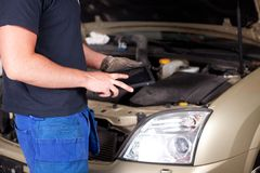 Mechanic with Digital Tablet. Detail of a mechanic with a digital tablet, car in background Stock Images