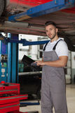 Mechanic with a digital tablet posing under the car. Mechanic standing under the car and holding a digital tablet Royalty Free Stock Image