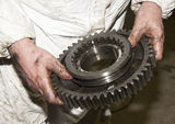 Mechanic dirty hands holds a big gear Stock Photo