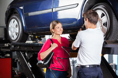 Mechanic Discussing With Customer While Filling Stock Photography