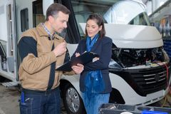Mechanic discussing motorhome repairs with woman. Mechanic discussing motorhome repairs with women mechanic royalty free stock photos
