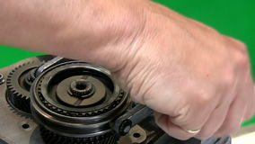 Mechanic dismantling gear box 2. Disassembling car gearbox. Close up of hands of mechanic unscrewing bolts and removing gear selector mechanism. Isolated on stock video footage