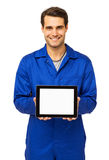 Mechanic Displaying Digital Tablet. Portrait of happy male mechanic displaying digital tablet over white background. Vertical shot Royalty Free Stock Image