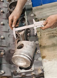 The mechanic does detail measurement before engine repair. Industrial platform. The mechanic does detail measurement. Engine repair Stock Image