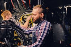 Mechanic doing bicycle wheel service manual in a workshop. stock images