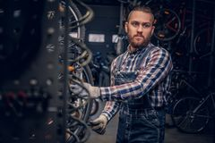 Mechanic doing bicycle wheel service manual in a workshop. stock photography