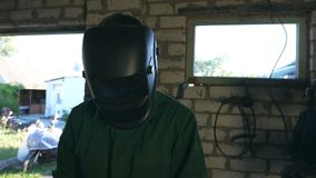 Mechanic doing his work using protective mask. Man in workwear worksin garage or workshop. Guy wears protective mask for