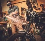 Mechanic doing lathe work in motorcycle customs garage Royalty Free Stock Images