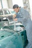 Mechanic doing up screw windshield on classic car Stock Photo