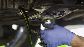 Mechanic draining oil from a car. Oil being drained from a car during an oil change Stock Images