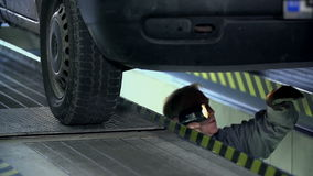 Mechanic is duing a maintainance service under a car stock video