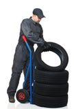 Mechanic on duty. Caucasian mechanic pose tire on handtruc isolated on white background stock photo