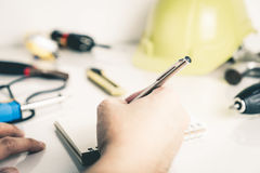 Mechanic engineer is writing on blank notebook Royalty Free Stock Images