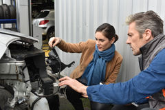 Mechanic estimating dammage and reparations to be done. Mechanics showing customer what is to repair on car Royalty Free Stock Images