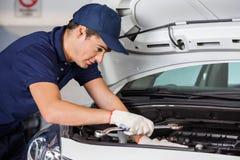 Mechanic Examining Car Engine Royalty Free Stock Image