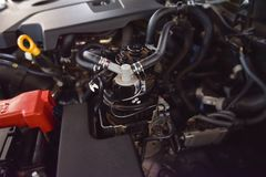 Mechanic Examining Car Engine At Repair Shop. Car service engine repair check up maintenance auto mechanic man tightened valve under hood car people hand fixing Royalty Free Stock Images