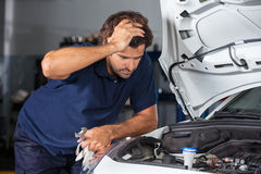 Mechanic Examining Car Engine At Repair Shop. Confused male mechanic examining car engine at auto repair shop Royalty Free Stock Photography