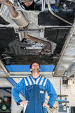 Mechanic Examining the state of an exhaust system Under The Car Royalty Free Stock Images