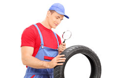 Mechanic examining tire through magnifying glass Royalty Free Stock Photos