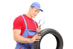 Mechanic examining tire through magnifying glass. Isolated on white background Royalty Free Stock Photos