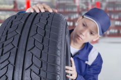 Mechanic examining tyre in the workshop Stock Photos